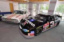 """At the N.C. Museum of History, members of the N.C. Sports Hall of Fame unveiled a #3 car (right, black car) driven by Dale Earnhardt Sr. Earnhardt's car appears near the 1963 Chevrolet Impala #3 (left, white car) that Robert """"Junior"""" Johnson drove during the 1963 NASCAR season. Photo credit: N.C. Museum of History"""