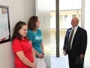 Christina Brock and Emily Cameron greet guests at the new residence halls.  President Philip Kerstetter stands in the doorway ready for a tour.