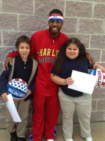 Ant Atkinson of the Harlem Globetrotters poses for a photo with 8-year-old twins Ryan and Amber Suffern. Ryan recently wrote a letter to Santa Claus asking to stop the bullying of his twin sister, Amber.