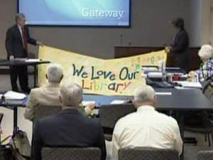 Wake County library supporters unfurl a sign at a June 1, 2009, Board of Commissioners meeting to lobby against proposed budget cuts.