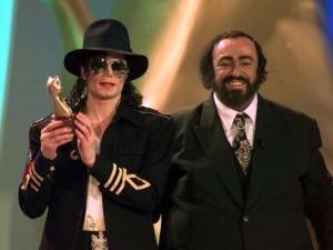 """US pop star Michael Jackson holds one of the Tv awards given during the """"Telegatti"""" (""""Tv Cats"""") international television award gala in Milan Monday night, May 5, 1997. At right is Italian tenor Luciano Pavarotti. They both attended as guests to the gala. (AP Photo/Luca Bruno)"""