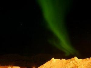The aurora borealis, or northern lights, dance over the town of Longyearbyen, Norway Thursday Feb. 28, 2008. The phenomenon is caused by an interaction between the earth's electromagnetic field and particles emitted from the sun. (AP Photo/John McConnico)