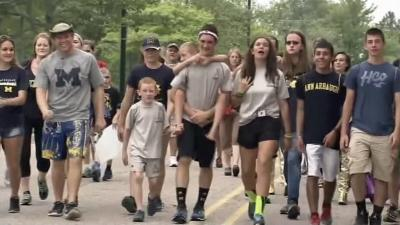 A 15-year-old Michigan boy walked 55 miles over the weekend with his younger brother on his back to raise awareness about cerebral palsy.
