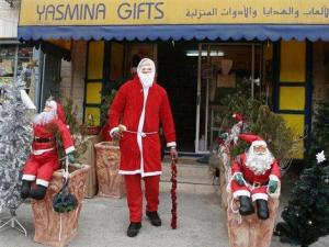 Khaled Rishmawi, 21-years-old, stands in his Santa Clause uniform in front of a local toy shop owned by a distant relative, Hana Rishmawi, in the West Bank town of Bethlehem, Tuesday, Dec. 4, 2007. Khaled is one of six Santa Clauses who will deliver presents to families around Bethlehem, and the nearby Christian villages of Beit Jala and Beit Sahour on Christmas. Hana Rishmawi hopes to scale-down the number of Santas he sends out, citing stress in administrating so much Christmas cheer.(AP Photo/Nasser Shiyoukhi)