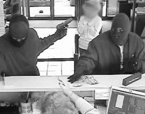 Surveillance photos taken of two masked men who threatened customers and robbed a Bank of America branch outside Crabtree Valley Mall on Friday afternoon.