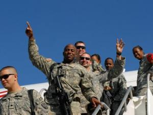Sgt. Melvin Kearney followed by Sgt. Eric R. Banks, both of the 1132nd, show their excitement as they exit an airplane after a long trip to the United States from Iraq. (photo by Capt. Christopher Joyner, Dept. Public Affairs Officer, NC National Guard)