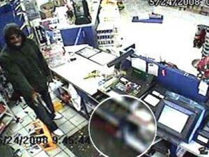 A security camera shows an armed man robbing Capital Food Mart on May 24, 2008. The robber is suspected in at least five hold-ups in Raleigh.