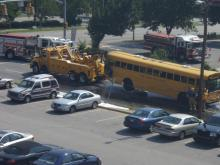 A Wake school bus is towed after catching fire at New Bern Avenue and Tarboro Street. (Photo by John R. Astle, N.C. DOT)