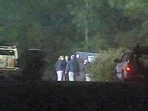 Law enforcement officials surround a rest stop on Interstate 40, near mile-marker 324, after a body was found Tuesday in a dumpster.