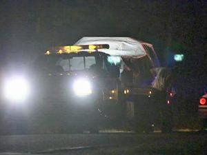A tow-truck crew loads a car covered by a tarp after a two-vehicle wreck at Campbells Street and Hunters Way in which two Angier police officers were injured late Saturday, May 2, 2009.