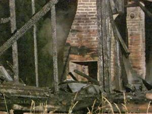 Smoke rises from the ruins of a house on Walter Myatt Road, near Kennebec Road in Fuquay-Varina. Firefighters say the fire, which started around 2:30 a.m. Friday, June 19, 2009, appears to have had a suspicious origin.