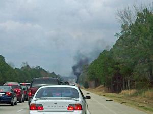 Black smoke from a vehicle fire rises above traffic stopped on Interstate 40 West, at mile marker 320, near Benson Sunday, March 21, 2010. (Photo by Matthew Opoka)