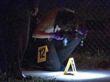 A Raleigh police officer examines a piece of evidence after a shooting at 913 S. Blount St. around 9:15 p.m. on Friday, April 30, 2010.