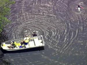 Harnett County authorities search a farm pond in Coats on July 21, 2010, for a teen who drowned.