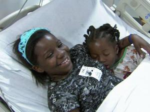 I'Doniya Brittian (right) snuggled with her sister in a hospital bed Monday. Doctors said she will make a complete recovery.