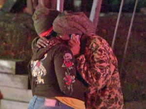 Two women comfort each other after a fire damaged a house at 2702 Poole Road in Raleigh early Sunday, Oct. 30, 2011.