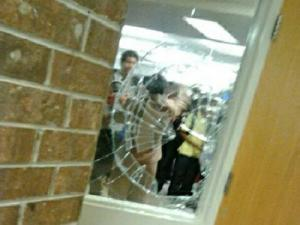 A broken window at Athens Drive High School in Raleigh, where police say an assistant principal was injured while trying to break up a fight. (Source: Twitter)