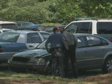 Police inspect the car used in a hit-and-run Saturday that killed a young woman.