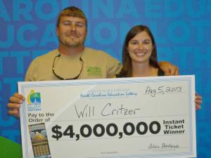 Will Critzer, of Sims, holds up a check signifying his $4 million win in the Gold Bullion game.
