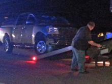 A man prepares to tow a Nissan pickup truck involved in a crash that injured two people on Nov. 14, 2013. Troopers said the injured had stopped on eastbound U.S. Highway 64 in Wake County when they were struck by the vehicle.