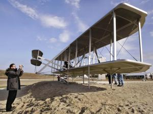 Sculptor Stephen Smith photographs his Wright flyer sculpture at the Wright Brothers National Memorial Saturday, Dec. 13, 2003, in Kill Devil Hills, N.C., during the First Flight Centennial to honor the Wright Brothers and 100-years of flight.(AP Photo/Bob Jordan)
