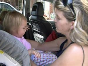 Parent Elizabeth Kimzey buckles her daughter into a child seat Monday.