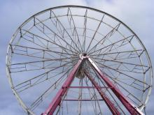 "A Ferris Wheel on the ""old midway"" waits patiently for some seats."