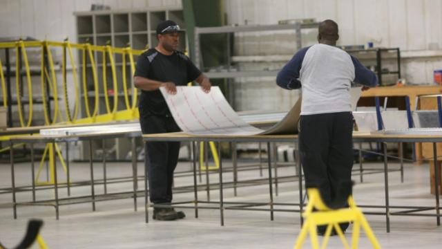 Employees of Allegro Light Sport Aircraft, in Littleton, N.C., work with a piece of sheet metal that will eventually become a plane wing. The company planned to hire 34 workers as part of an incentive grant. (Photo by Tyler Dukes)