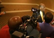 WRAL News photographer rolls tape while reporter Bruce Mildwurf talks to GOP primary presidential candidate Herman Cain, who spoke to the North Carolina delegation Monday morning.