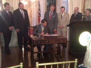 House Speaker Thom Tillis and Senate leader Phil Berger look on as Gov. Pat McCrory signs the 2013 tax bil into law.