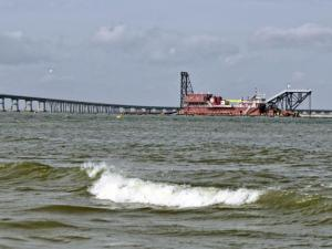 A dredge begins the process of shoring up the Bonner Bridge against underwater erosion on Dec. 6, 2013. The N.C. Department of Transportation closed the bridge three days earlier, saying the erosion made the span vulnerable to collapse. (Photo by Donnie Bowers)
