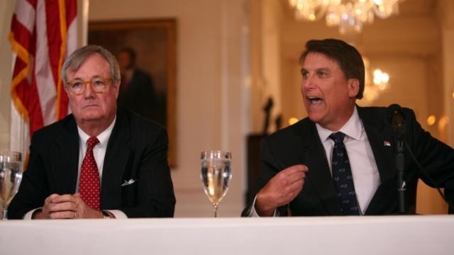 John Skvarla, the former secretary of the Department of Environment and Natural Resources who took the helm of the commerce department this year, listens to Gov. Pat McCrory speak at a news conference at the governor's mansion on Jan. 21, 2014. (Kelly Hinchcliffe/WRAL)