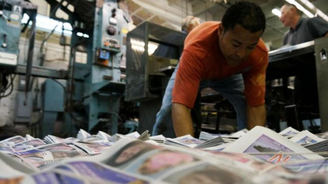 Felix Montero stacks copies of the NC Slammer at Triangle Web Printing in Durham, N.C. The paper, contracts with the company to print thousands of copies covering arrests in Raleigh, Durham and Johnston counties (Tyler Dukes/WRAL).