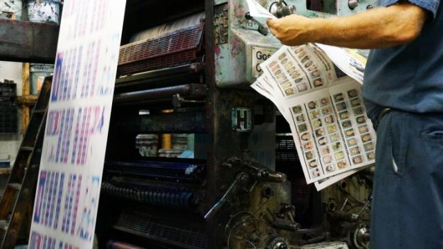 An employee of Triangle Web Printing in Durham, N.C., thumbs through a copy of the NC Slammer on June 17, 2014. (Tyler Dukes/WRAL)