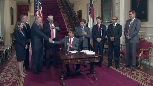 McCrory dismisses critics in signing state budget