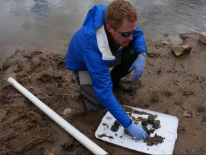Pete Harrison, a staff attorney with the Waterkeeper Alliance, expamines core samples taken from the Dan River near Milton on Jan. 30, 2015. The samples show a layer of coal ash between layers of clay and sediment.