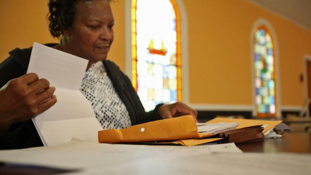 Yadkin Grove Baptist Church Deacon Osheatia Roberson thumbs through documents she's received about the quality of her church's well water (Tyler Dukes/WRAL).