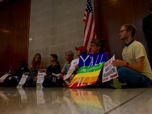 House Bill 2 opponents sit outside the office of House Speaker Tim Moore during an April 25, 2016, protest calling for a repeal of the controversial law.