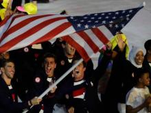 Ibtihaj Muhammad waves to crowd as she marches with fellow USA olympians at the opening ceremonies in Rio.