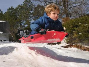 Our son John caught some big air on his friend's sled this morning.  Everyone took turns hitting the ramp and trying to get the biggest air.