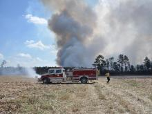 A brush fire burned through a cornfield and woods near Crocker and Daughtry roads in Smithfield on Monday afternoon, according to the North Carolina Division of Forest Resources.