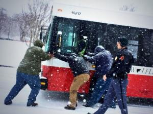A group works to push a stuck Wolfline bus near N.C. State in Raleigh Wednesday. Photo by Aysu Basaran