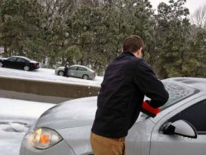 A Triangle residents scraps his car on Glenwood Avenue in Raleigh on Thursday, Feb. 13, 2014.