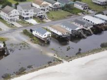 Days of heavy rain and the passing offshore of Hurricane Joaquin pushed waves and sand onto roads in Buxton. Other coastal communities, including Ocean Isle, Atlantic Beach and Swansboro, experienced flooding.