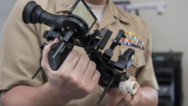 A United States Naval Academy instructor holds a sextant during classroom instruction on celestial navigation (Credit: U.S. Navy/Tyler Caswell)