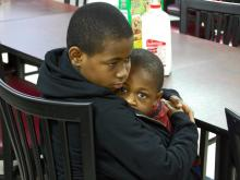 """Ten-year-old """"C"""" holds his 4-year-old brother at the Raleigh Rescue Mission, where they live."""