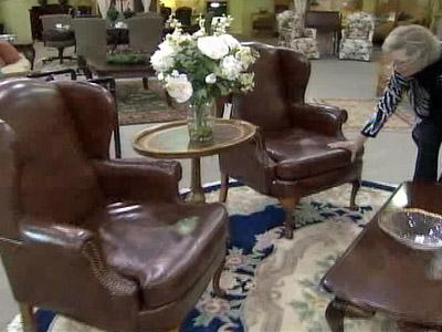 Consigning Design in Cary owner Sandy West inspects wingback chairs for sale at the store.