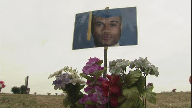 A laminated photo taped to a wooden stick serves as a makeshift grave marker for Alex Bryant.