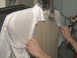 A standard machine used by dry cleaners is made to fit a man's shirt. Women's blouses must often be pressed by hand.