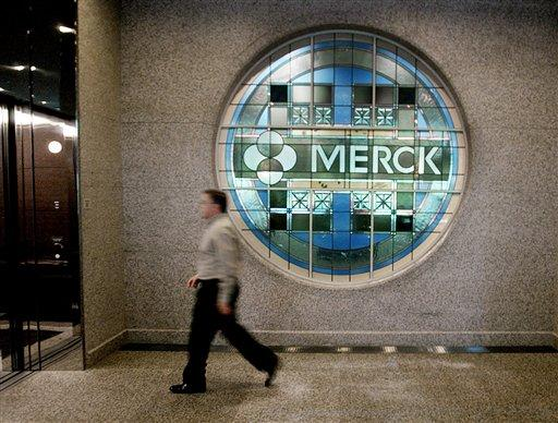 An employee passes a stained-glass window, bearing Merck & Co.'s name, at the company's headquarters in a Whitehouse Station, N.J., file photo from Sept. 30, 2004. (AP Photo/Daniel Hulshizer, File)